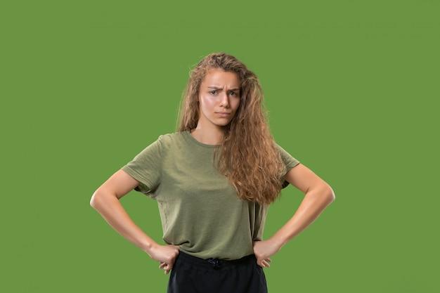 Donna seria di affari che sta e che esamina macchina fotografica contro il verde