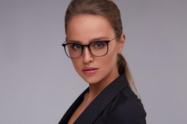 Donna seria elegante in occhiali quadrati bella donna di affari adulta in vestito