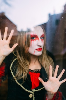 Donna seria in costume da strega pone dietro il vetro