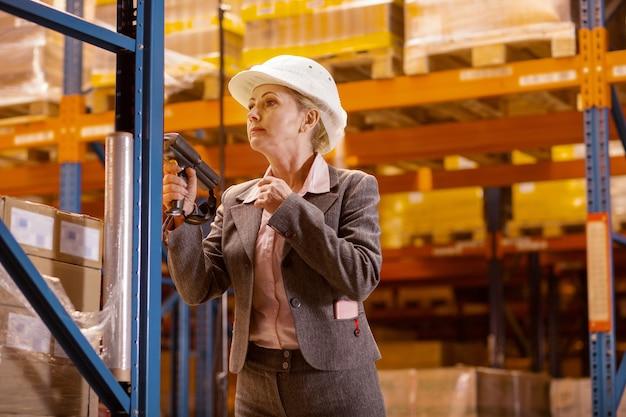 Donna seria piacevole che indossa un casco mentre aderisce alle norme di sicurezza nel magazzino