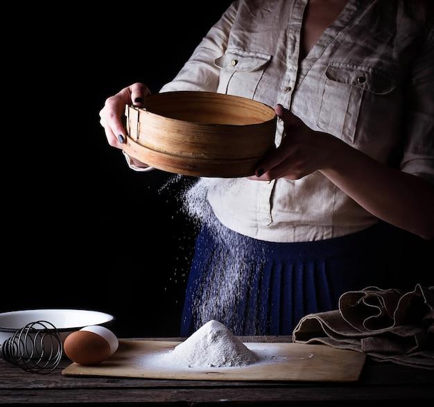 Donna setacciare la farina al setaccio