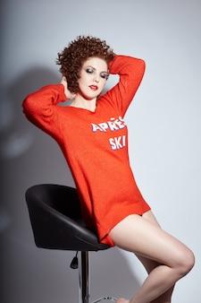 Donna sexy adulta rossa riccia in maglione rosso