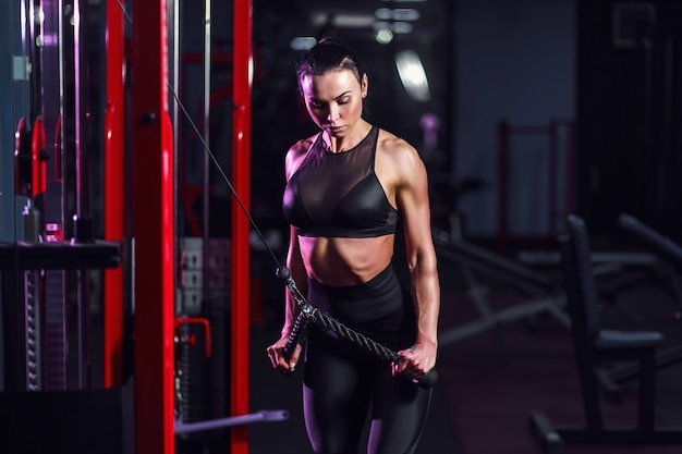 Donna sexy atletica che fa esercizio facendo uso della macchina nella palestra - vista laterale