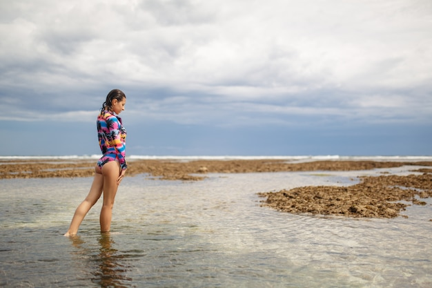 Donna sexy che propone alla spiaggia dell'oceano