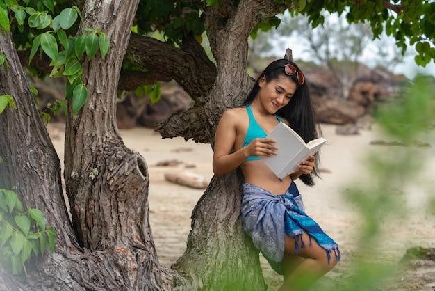 Donna sexy che sorride leggendo un libro sotto gli alberi sulla spiaggia