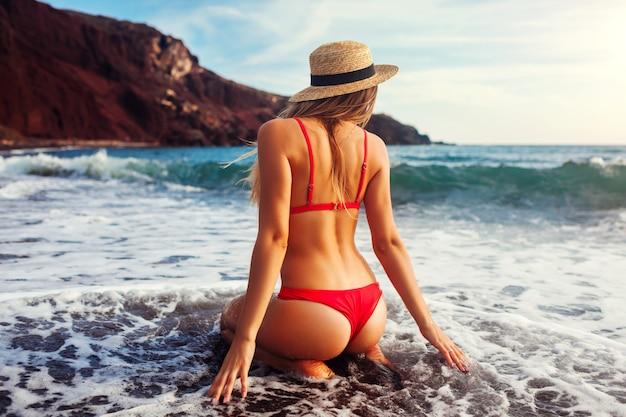Donna sexy in bikini che si distende sulla spiaggia