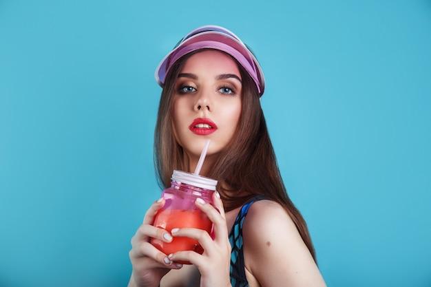 Donna sexy in costume da bagno e visiera di plastica che tiene vetro di fresca bevanda estiva sulla parete blu
