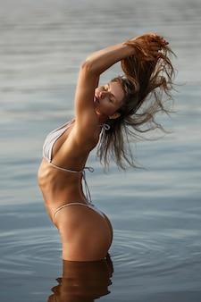 Donna sexy in costume da bagno sulla riva del fiume