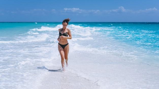 Donna sexy nell'usura di nuotata che sta nell'oceano