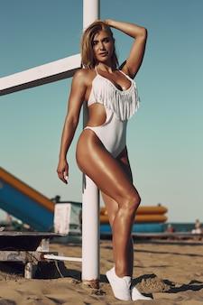 Donna sexy stupefacente in costume da bagno bianco con l'ente sportivo perfetto che posa sulla spiaggia. concetto di sport womans body in costume da bagno