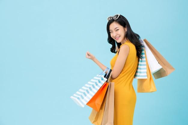 Donna shopaholic asiatica che trasporta i sacchetti di acquisto variopinti
