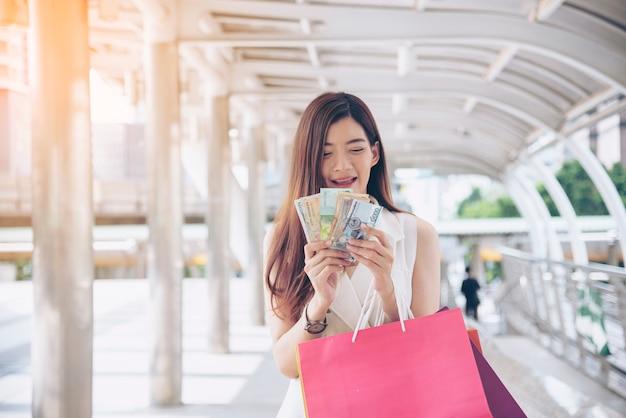 Donna shopaholic che tiene i sacchetti della spesa, soldi, carta di credito ai centri commerciali