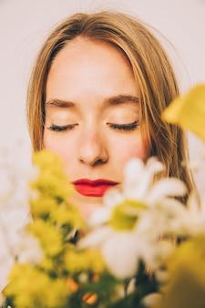 Donna sicura attraente che si leva in piedi dietro le fioriture fresche