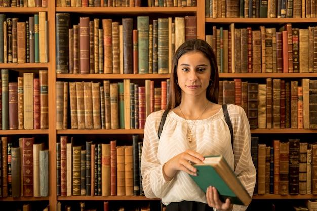 Donna sicura che guarda l'obbiettivo contro lo scaffale per libri