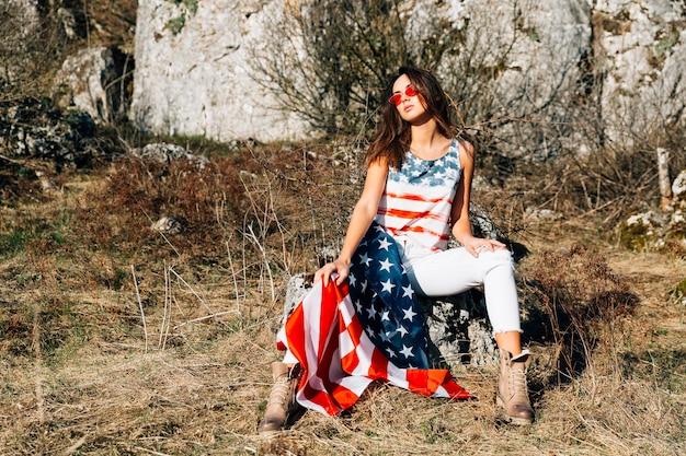 Donna sicura con la bandiera di usa che si siede sulla pietra