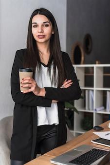 Donna sicura con la bevanda in ufficio