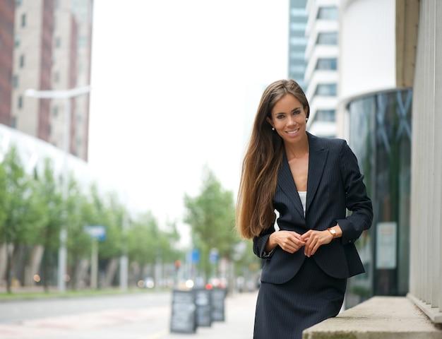Donna sicura di affari che si leva in piedi all'aperto