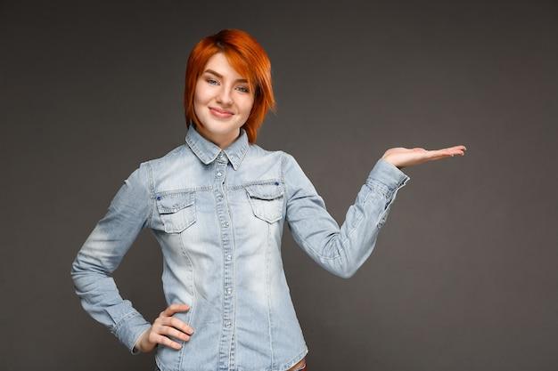 Donna sicura di redhead che presenta prodotto, che punta a destra