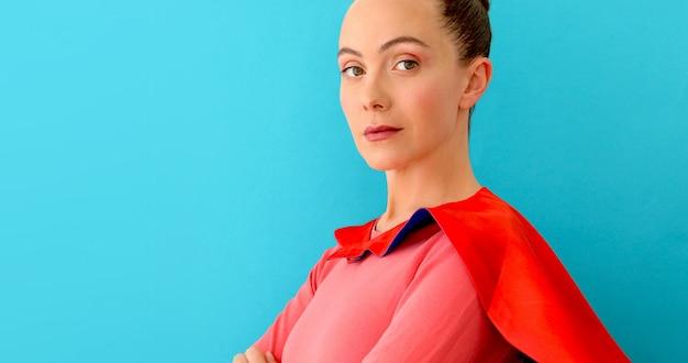 Donna sicura di sé in mantello rosso, supereroe