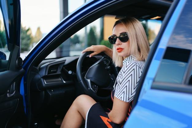 Donna sicura e bella in occhiali da sole. vista posteriore della giovane femmina attraente in abbigliamento casual alla guida di un'auto