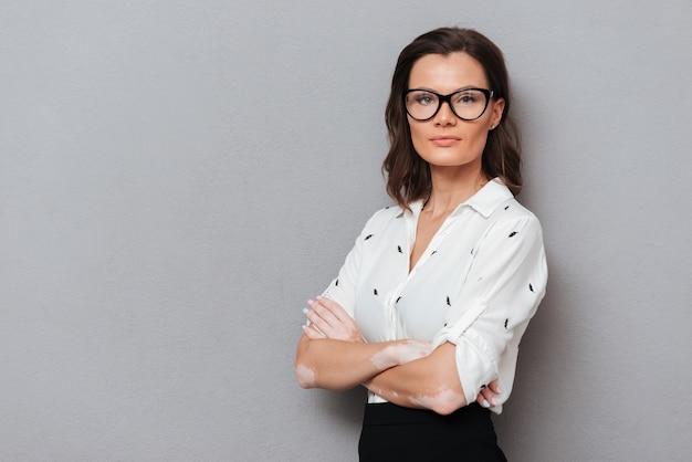 Donna sicura in occhiali e abiti d'affari in posa con le braccia incrociate e guardando la telecamera su grigio