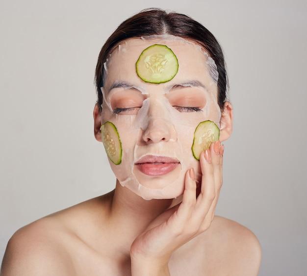 Donna sofisticata in una maschera idratante con un cetriolo fresco sul viso nella serena bellezza calma con gli occhi chiusi e la mano sinistra vicino al viso