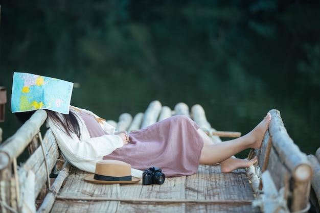 Donna sola che si siede sulla zattera di lungomare