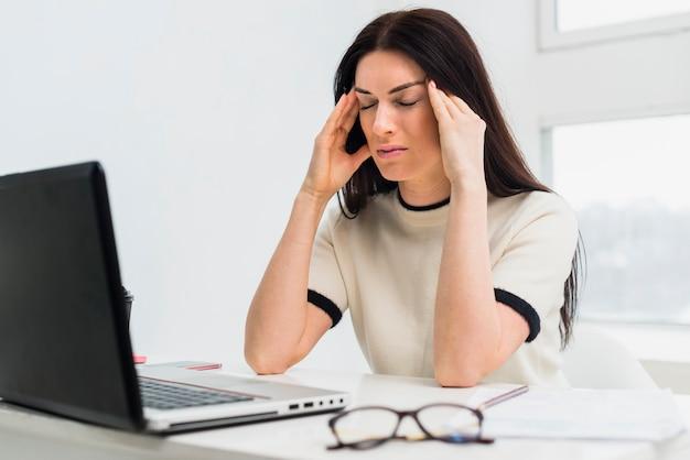 Donna sollecitata che si siede alla tabella con il computer portatile