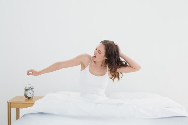 Donna sonnolenta che allunga le braccia e sbadiglia nel letto