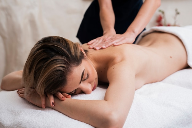 Donna sonnolenta che ottiene massaggio alla schiena
