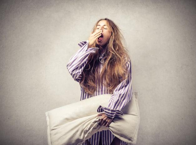 Donna sonnolenta con un cuscino