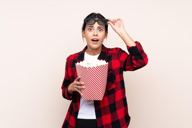 Donna sopra il muro sorpreso con gli occhiali 3d e in possesso di un grande secchio di popcorn