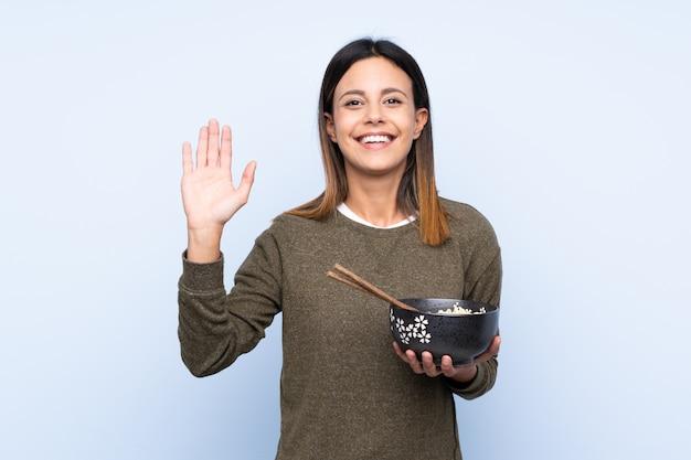 Donna sopra la parete blu isolata che saluta con la mano con l'espressione felice mentre tenendo una ciotola di tagliatelle con le bacchette