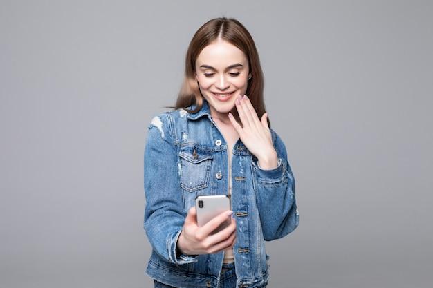 Donna sorpresa che copre la bocca, guardando lo schermo del telefono cellulare, scioccata lettura femminile messaggio imprevisto, offerta commerciale, buone notizie, tenendo il cellulare, isolato sul muro grigio