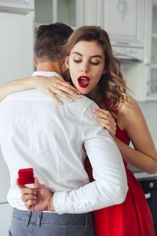 Donna sorpresa che esamina scatola con l'anello di fidanzamento in sue mani del marito