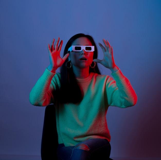 Donna sorpresa che indossa i vetri 3d del cinema alla luce blu e rossa