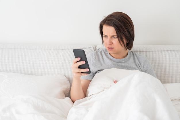 Donna sorpresa che per mezzo dello smartphone mentre si siede nel letto coperto di piumone