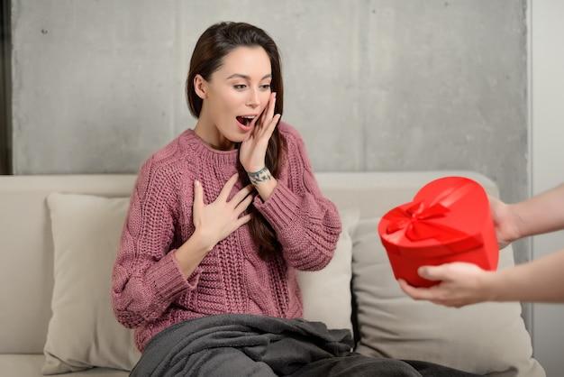 Donna sorpresa che riceve una confezione regalo a forma di cuore dalle mani del suo ragazzo. l'uomo fa un regalo alla ragazza