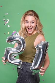 Donna sorpresa con un cartello a 21 palloncini