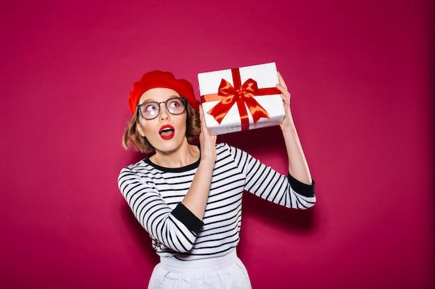 Donna sorpresa dello zenzero intrigata in occhiali che tengono il contenitore di regalo vicino all'orecchio e che distoglie lo sguardo sopra il rosa
