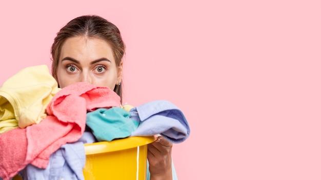 Donna sorpresa primo piano con il cestino di lavanderia