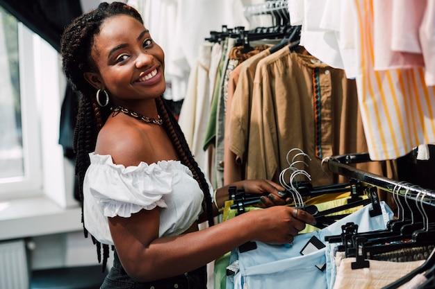 Donna sorridente a fare shopping nel negozio di abbigliamento