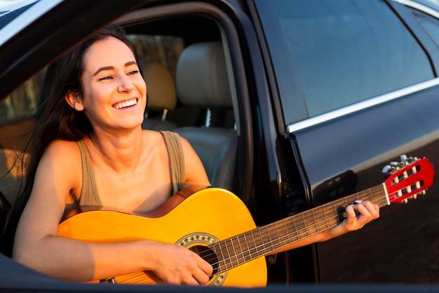 Donna sorridente a suonare la chitarra fuori dalla sua auto mentre all'aperto