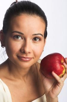 Donna sorridente abbastanza giovane con la mela rossa.