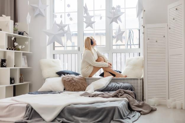 Donna sorridente abbastanza sexy che si siede nel letto la mattina, ascoltando la musica in cuffia
