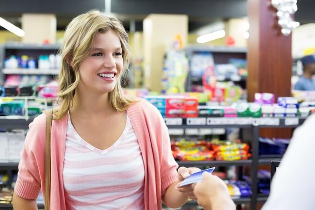 Donna sorridente al registratore di cassa pagando con carta di credito