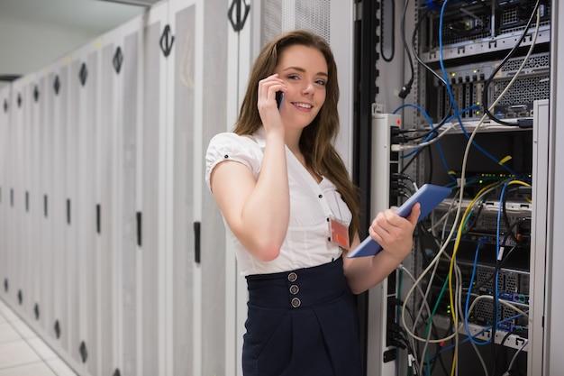 Donna sorridente al telefono tenendo il tablet pc e controllando i server