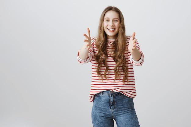 Donna sorridente allegra che raggiunge le mani davanti, tenendo qualcosa