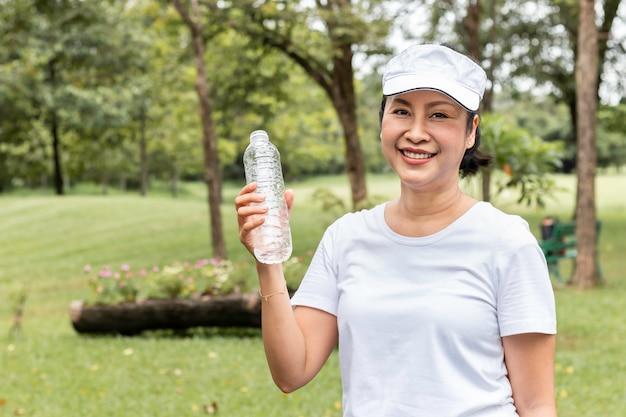Donna sorridente asiatica anziana felice che beve acqua dolce di estate al parco.