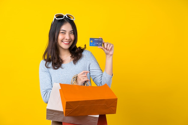 Donna sorridente asiatica felice che presenta la carta di credito e che porta una borsa coloful di compera per la presentazione dell'acquisto online sulla parete gialla isolata